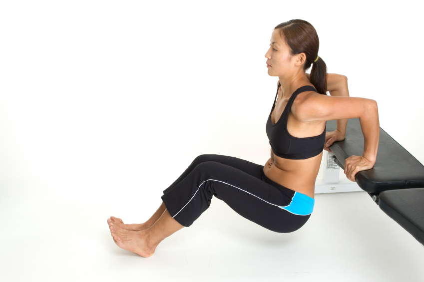 A female fitness instructor demonstrates the finishing position of the tricep bench dips