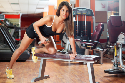 Beautiful young woman exercising with dumbells in the gym. Shallow depth of field