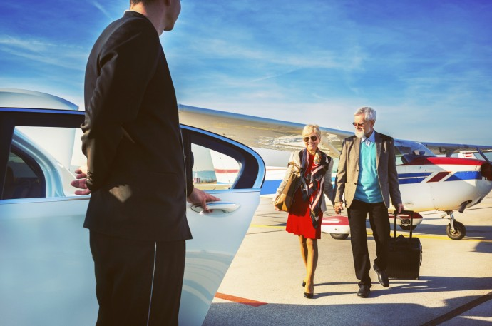 Driver helping senior adult couple into limousine at airport