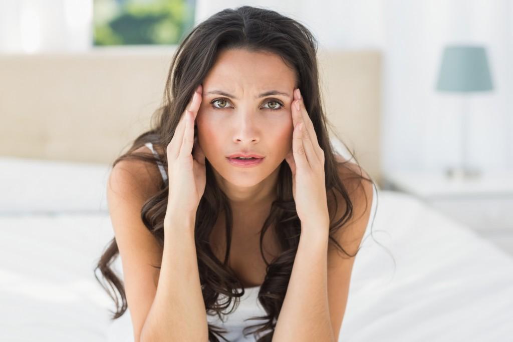 Worried brunette sitting on bed