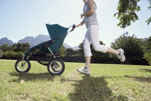Woman Running with Baby Carriage in Park