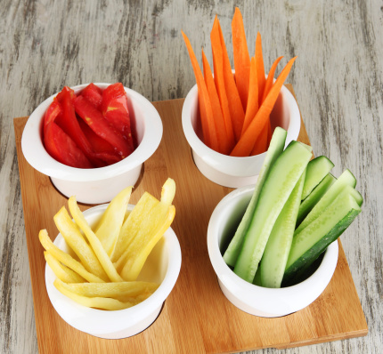 Fresh vegetables cut up slices in bowls on wooden table