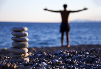 Man praying on the beach and Stones balance .