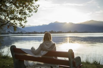 Woman sitting on bench by the lake contemplating nature
