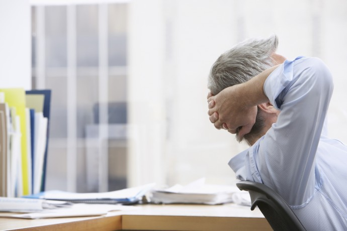 Business man with hands behind head in office
