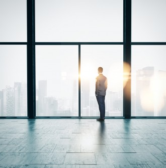 Businessman looking at sunrise in the loft