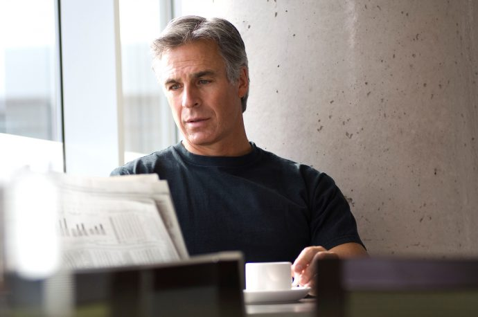 Gray haired middle aged man reading newspaper in cafe on weekend.