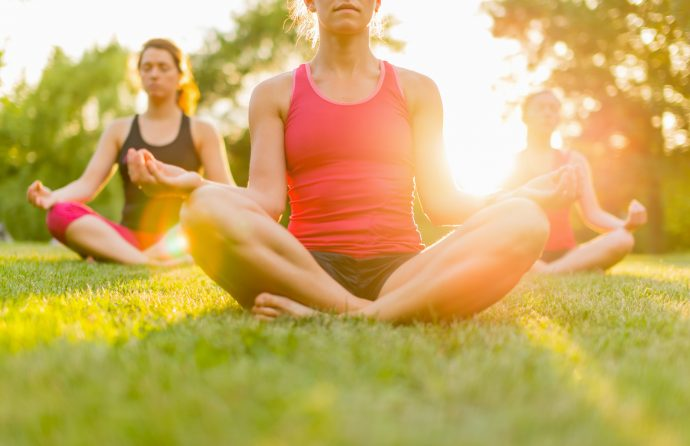 A closeup of a woman doing yoga outside with two other women