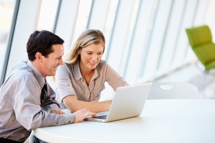 A man and a woman work in front of a laptop in an office