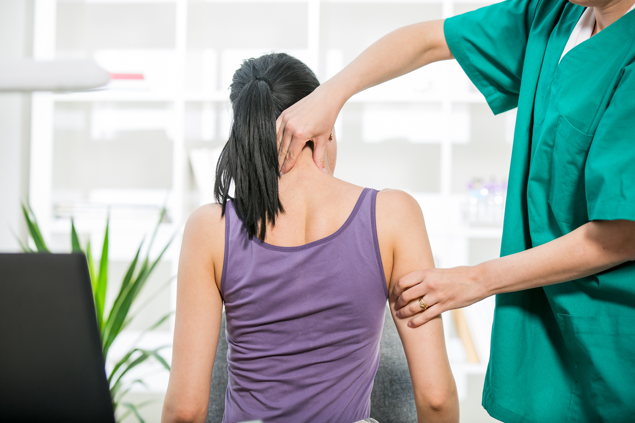 Chiropractor stretches female patient neck muscles